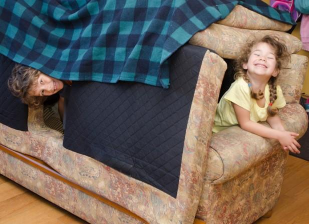 Deux enfants ont fait une cabane avec les coussins du fauteuil